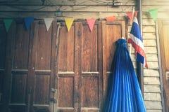 Antik trädörr på det thailändska huset för tappning med den Thailand flaggan Royaltyfria Bilder