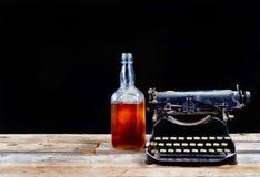 Antik Typerwriter och whiskyflaska Arkivbilder