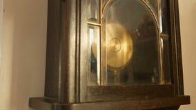 Antik väggklocka med en klockpendel Hand för man` som s stoppar klockpendeln, closeup stock video
