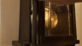 Antik väggklocka med en klockpendel Handen för man` s startar klockpendeln, closeup lager videofilmer