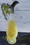 Antik vinkanna med sidor för vitt vin och druva Arkivfoto
