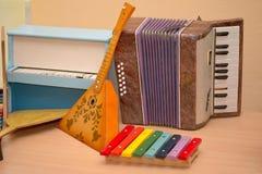 Antika antika leksakmusikinstrument balalajka, dragspel, H Arkivbilder