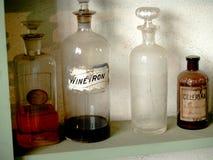 Antika apotekaresmå medicinflaskor på en hylla Royaltyfria Bilder