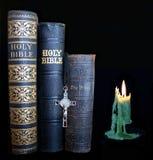 Antika biblar bredvid bränt ner att bränna den gröna stearinljuset arkivfoton