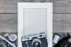 Antika kameror, negativa filmer och vit tom fotoram på w Arkivfoto