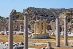 Antika kolonner med delen av amfiteatern i sidan för forntida stad, Turkiet arkivfoton