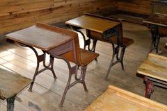 Antika skrivbord i klassrum Arkivfoto