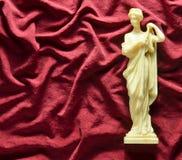 Antike Andenkenstatue der griechischen Göttin auf einem roten silk Hintergrund Kopieren Sie Platz Stockfotografie