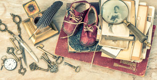 Antike Bücher und Fotos, Schlüssel, Babyschuhe und Schreiben accessori Stockfotografie