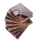 Antike Bücher und Vergrößerungsglas des Stapels Stockfotografie