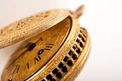 Antike gelbe Messingtaschenuhr auf Weiß Stockbild