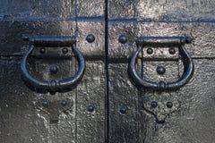 Antike geschmiedete Griffe auf dem Tor stockbilder