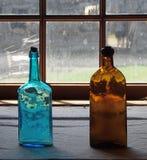 Antike Glasflaschen im Fenster Stockbilder