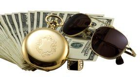 Antike Golduhr, Goldsonnenbrillen und Stapel Gelddollar stellten lokalisiert ein Stockfotos