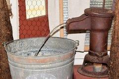 Antike manuelle Handwasserpumpe und Eimer Wasser Stockfotografie