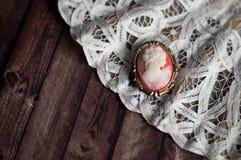 Antike Miniaturbrosche auf Spitzefan Lizenzfreies Stockfoto