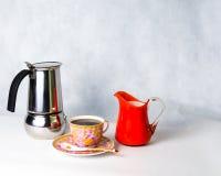 Antike Schale, Untertasse, Milch in einer Glasgefäßorange und Kaffeetopf Stockfotografie
