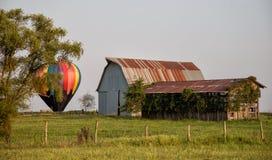 Antike Scheune auf einem Gebiet mit einem bunten Heißluftballon lizenzfreies stockfoto