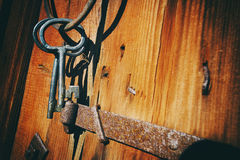 Antike Schlüssel gegen alte hölzerne Wand Stockfotografie