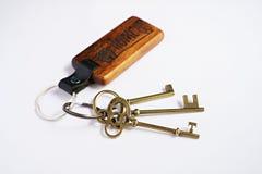 Antike Schlüssel mit hölzernem Schlüsselring des Hauses mit weißem Hintergrund Lizenzfreie Stockfotografie