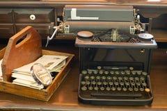 Antike Schreibmaschine, die auf einem Desktop mit einem Briefkasten und einer alten Lupe sitzt Stockfotografie