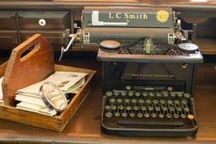 Antike Schreibmaschine, die auf einem Desktop mit einem Briefkasten und einer alten Lupe sitzt Stockbild