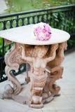 Antike Statue, die eine Tabelle mit Heiratsblumenstrauß stützt lizenzfreies stockfoto