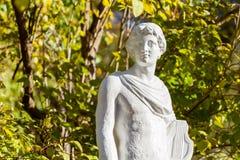 Antike Steinskulptur auf Hintergrund von grünen Bäumen Stockfotos
