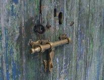 Antike Tür mit beunruhigtem Farbenende im Blau und in den Grüns mit Messingtürmöbeln Stockbild