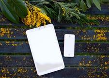 Antike Tabelle mit Mobile, Tablette und gelben Wildflowers stockfoto