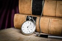 Antike Taschenuhr auf burled Holz mit alten ledernen gebundenen Büchern und Füllfederhalter lizenzfreie stockbilder