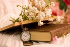 Antike Taschenuhr, geöffnete Bücher, Blumen Stockbild