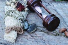Antike Taschenuhr und -Sanduhr mit Trockenblumen Stockbild