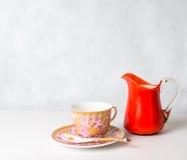 Antike Tasse und Untertasse und Milch in einer Glasgefäßorange Lizenzfreie Stockfotografie