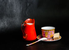 Antike Tasse und Untertasse und Milch in einer Glasgefäßorange und -oblate Stockfotos