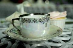 Antike Teeschale auf dem Tisch mit Hintergrund des kleinen Kuchens Stockfotos
