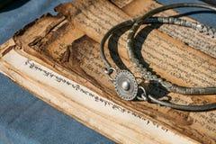 Antike tibetanische Bronzejuwelen und alte betende Bücher Lizenzfreies Stockbild