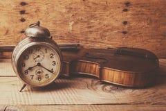 Antike Uhr und alte Violine über Weinleseholztisch Stockfotografie