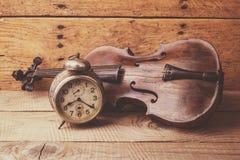 Antike Uhr und alte Violine über Weinleseholztisch Stockfoto