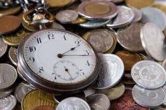 Antike Uhr und Münzen lizenzfreies stockbild