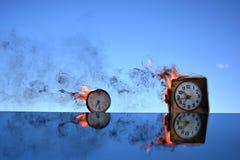Antike Uhr zwei, die im Raum auf Spiegel, Zeitkonzept brennt Stockfotos