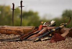 Antike Waffen, die aus den Grund liegen Pfeile, Bogen, Säbel, der auf einem hölzernen braunen Klotz liegt lizenzfreie stockfotografie