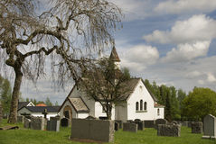Antike weiße Kirche auf altem Kirchhof. Stockfotos
