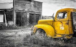 Antiker alter LKW mit dem gelben Fahrerhaus, das durch eine alte Garage sitzt Stockfotografie