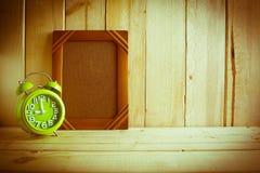 Antiker Fotorahmen und -uhr auf Holztisch über hölzernem Hintergrund Stockfotos