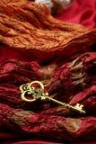Antiker goldener Schlüssel auf rotem Luxusgewebe Stockbilder