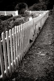 Antiker hölzerner weißer Palisadenzaun und alter Garten Stockfotos