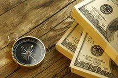Antiker Kompass und Geld auf hölzerner Tabelle Lizenzfreie Stockfotos