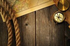 Antiker Kompass und Seil über alter Karte Stockfotografie