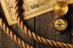 Antiker Kompass und Seil über alter Karte Stockfoto